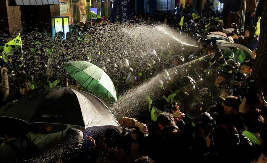 Police officers spray liquid at demonstrators during a commemoration in Seoul of the Sewol sinking. Photo: Lee Jin-man / Associated Press / AP