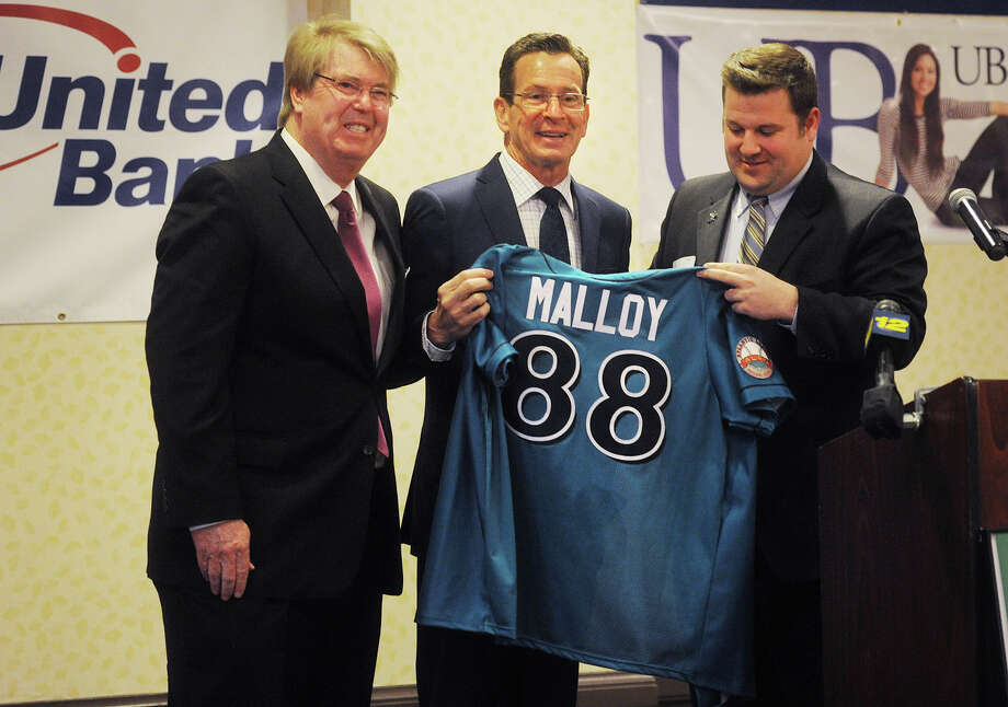 Governor Dannel P. Malloy, center, receives a personalized Bridgeport Bluefish baseball jersey from team owner Frank Boulton, left, and General Manager Jamie Toole during the Bridgeport Regional Business Council's Capitol Luncheon at the Holiday Inn  in Bridgeport, Conn. on Thursday, April 16, 2015. Photo: Brian A. Pounds / Connecticut Post