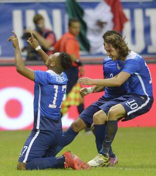 Juan Agudelo of the USA is greeted by teammates Mix Diskerud (10) and DeAndre Yedlin after scoring a second-half goal during an international friendly match against Mexico at the Alamodome on Wednesday, April 15, 2015. Photo: Billy Calzada, Staff / San Antonio Express-News / San Antonio Express-News