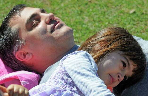 Joe Tocci and his 4-year-old daughter Gianna Tocci both of Saratoga Springs relax with their family in Congress Park on Thursday April 16, 2015 in Saratoga Springs, N.Y. (Michael P. Farrell/Times Union) Photo: Michael P. Farrell