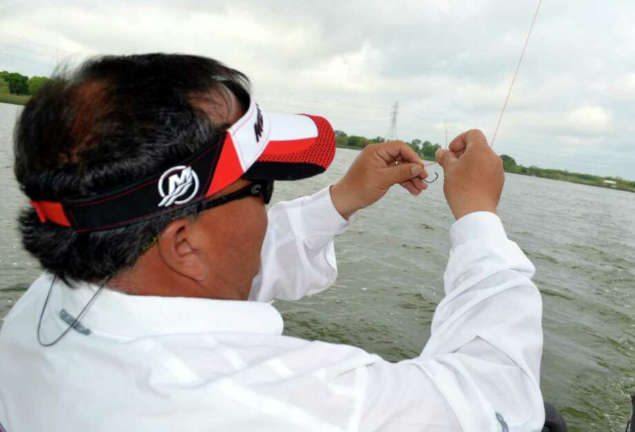 The right fishing line like this Cajun Red Cast Premium monofilament leader being tied to a lure by Guide Manny Martinez can often be the key to catching big redfish at Braunig Lake. Photo: Ralph Winningham / For The Express-News