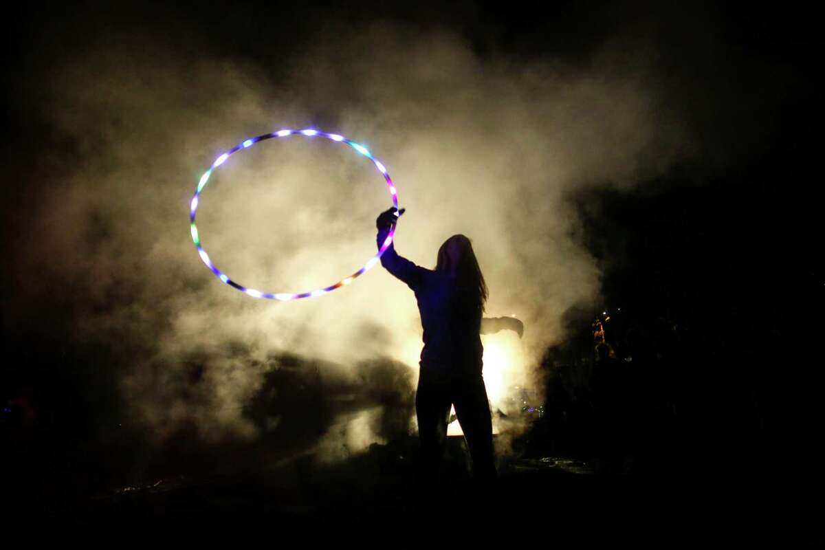 A woman that goes by the name Manda Panda performs with a hoop as a bonfire smolders on Thursday, January 8, 2015 at Golden Gardens Beach Park.