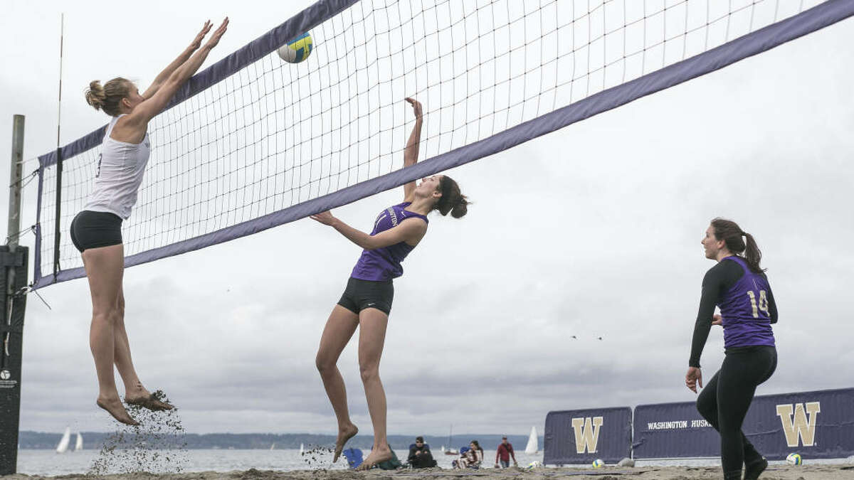 Kaleigh Nelson, center, goes for a block against Katy Beals in the intrasquad opener of UW Sand Volleyball at Golden Gardens in Seattle on April 5, 2014.