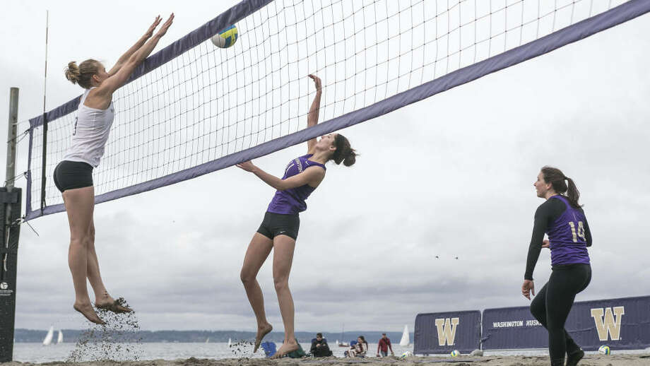 Kaleigh Nelson, center, goes for a block against Katy Beals in the intrasquad opener of UW Sand Volleyball at Golden Gardens in Seattle on April 5, 2014. Photo: Seattlepi / Photo courtesy UW Athletics