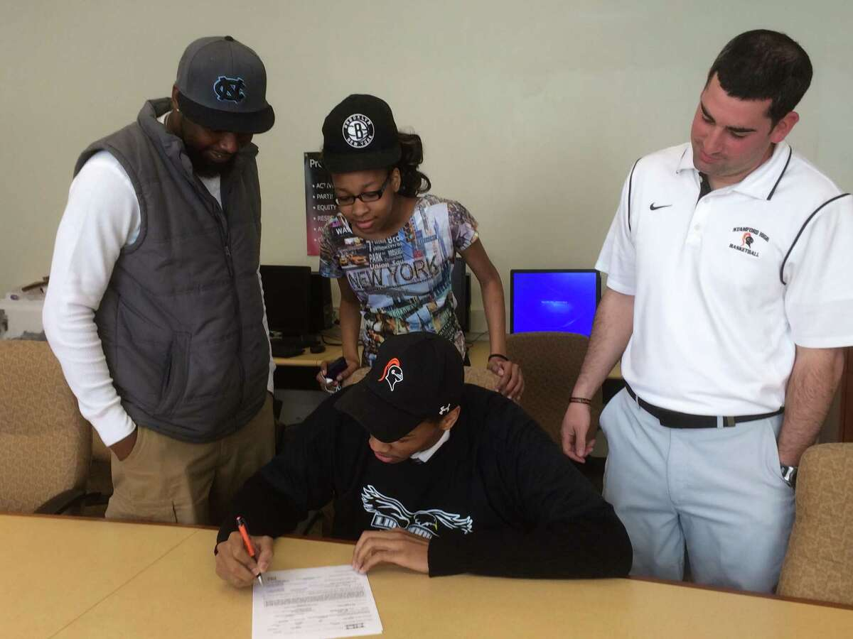 Stamford basketball player Kwe Askew signs his NLI to play at LIU Brooklyn. He is surrounded by Stamford coach Danny Melzer, his sister Knadria and father Lorenzo at Stamford High School's Professional Library on April 16, 2015.