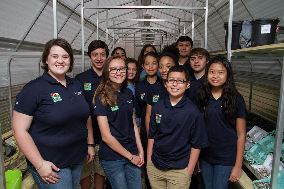 Loryn Windwehen with her Green Team class at Harris Middle School, Friday, April 10, 2015. Windwehen, who teaches science, created the Green Team, a club that meets as an elective class, to oversee the garden that includes a greenhouse, a hydroponic growing area and vegetable beds. Photo: Alma E. Hernandez /For The Express-News