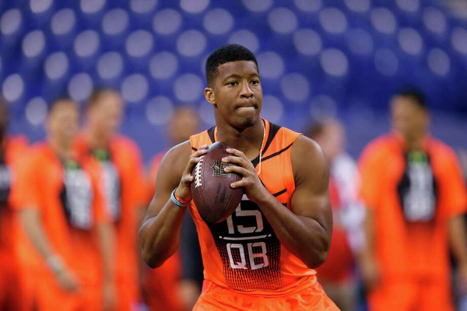 In this Feb. 21, 2015, file photo, Florida State quarterback Jameis Winston runs a drill at the NFL football scouting combine in Indianapolis. While 26 draft-eligible players have accepted invitations from the NFL to attend the proceedings later this month, Winston and Marcus Mariota are not among them. The two most recent Heisman Trophy winners and highest-profile players in this year's crop have opted to stay home with their families for the April 30-May 2 draft. Photo: Julio Cortez /Associated Press / AP