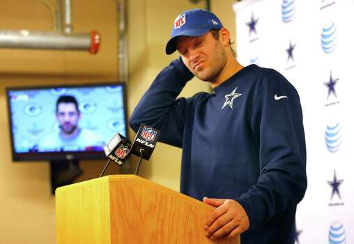 Dallas Cowboys quarterback Tony Romo (9) listens to a question from a reporter as Green Bay Packers quarterback Aaron Rodgers delivers his remarks on television after the NFC Divisional playoff game at Lambeau Field in Green Bay Wisconsin, Sunday, January 11, 2015. The Cowboys lost 26-21. Photo: Tom Fox /Dallas Morning News / The Dallas Morning News