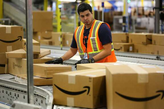 A worker at the Amazon Fullfillment Center in Schertz, TX, inspects packaging on a conveyor belt.  Thursday, April 16, 2015.