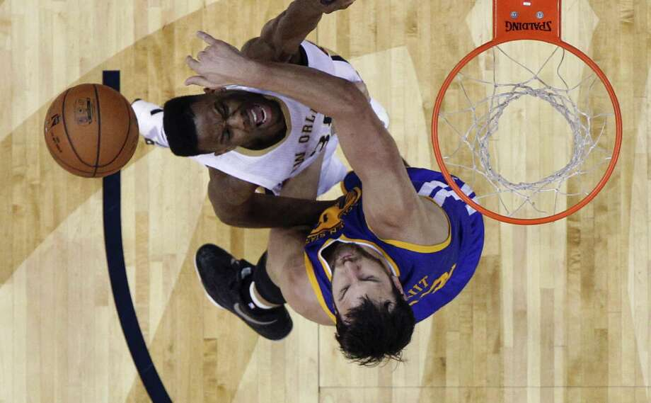 New Orleans Pelicans guard Norris Cole, left, is topped as he drives to the basket against Golden State Warriors center Andrew Bogut in the first half of an NBA basketball game in New Orleans, Tuesday, April 7, 2015. (AP Photo/Gerald Herbert) Photo: Gerald Herbert, STF / Associated Press / AP
