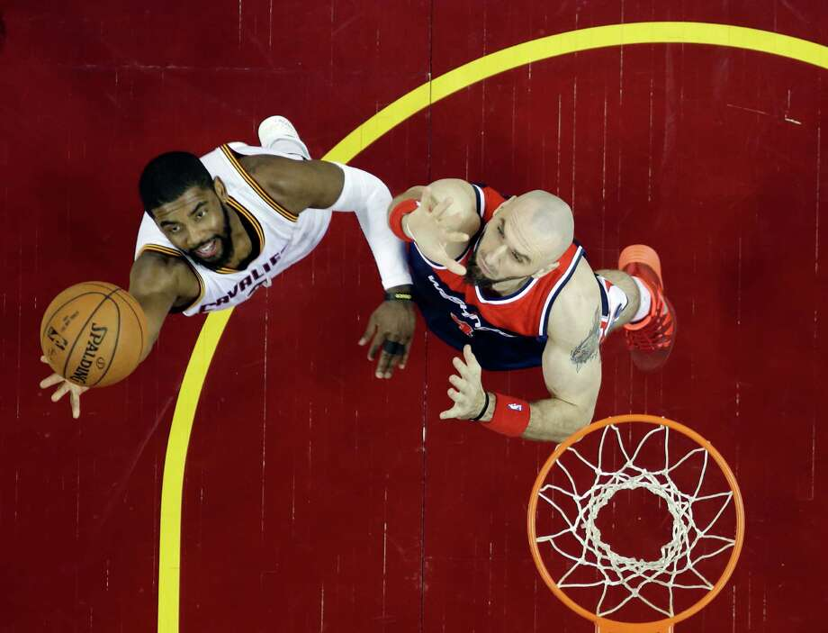 Cleveland Cavaliers' Kyrie Irving, left, shoots over Washington Wizards' Marcin Gortat in an NBA basketball game Wednesday, April 15, 2015, in Cleveland. (AP Photo/Mark Duncan) Photo: Mark Duncan, STF / Associated Press / AP