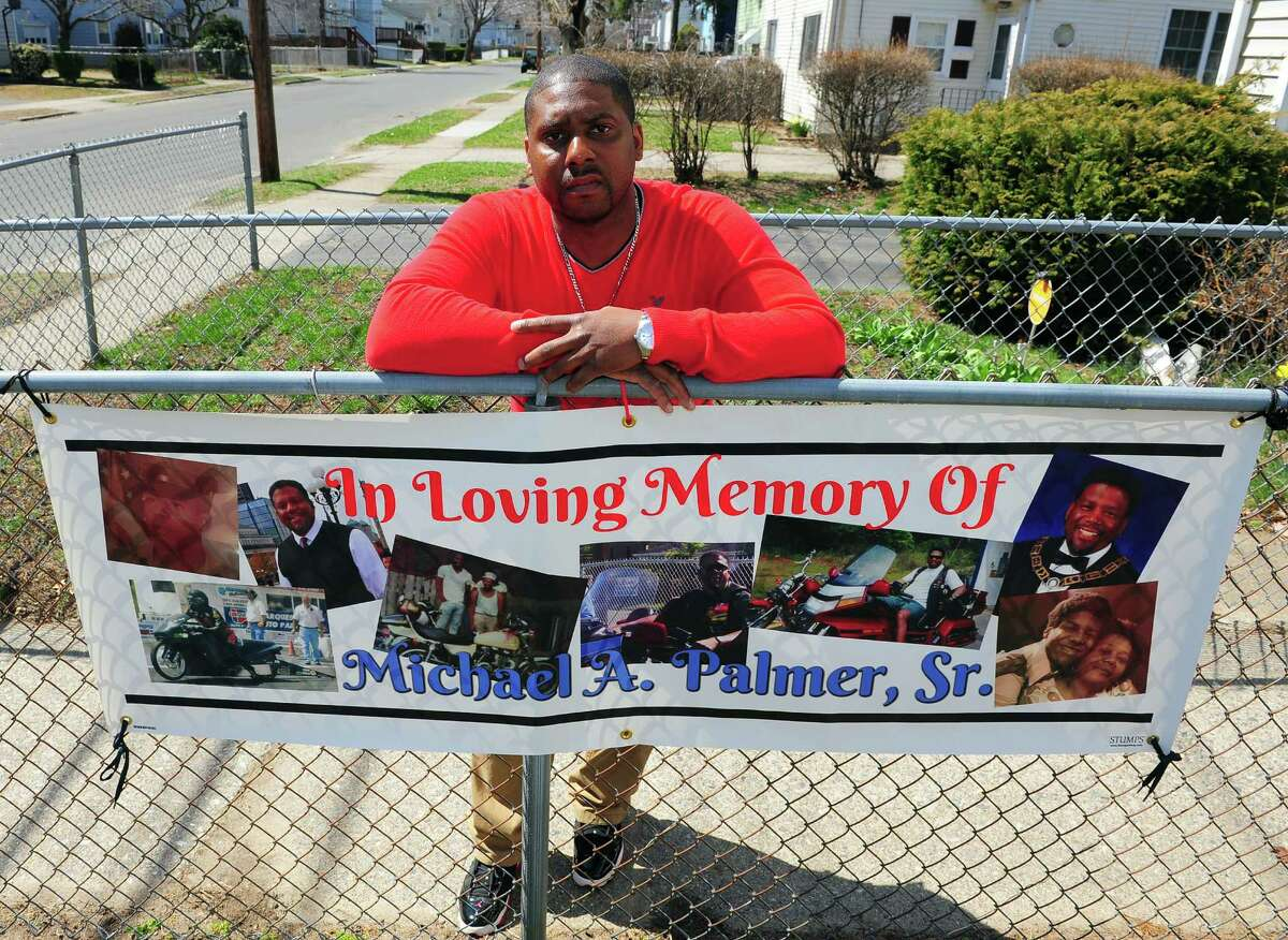 Michael Palmer II poses with a banner he had made in memory of his dad Michael Sr. at his home on Columbus Avenue in Stratford, Conn., on Thursday Apr. 16, 2015. Palmer Sr. died in 2013 following a surgical procedure at an outpatient facility in Trumbull. The family is suing the clinic, alleging negligence and other malfeasance.