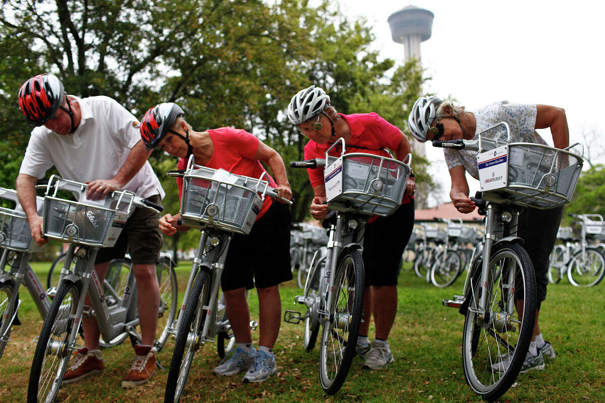 Glenn Jensen, from left, Vicki Roberson, Vicki Smith and Bonnie Barstow look at the extra lock on the bikes as they prepare to ride the B-cycles from the San Antonio B-cycle HUB to the B-cycle stations around downtown San Antonio.