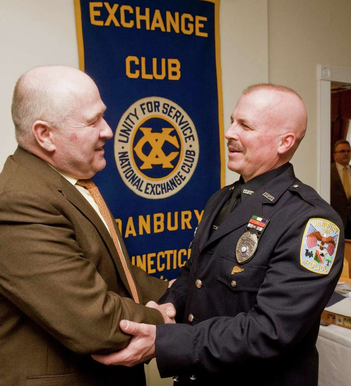 Danbury police chief Alan Baker, left, congratulates Danbury police Officer Joseph Pooler who is being honored as City of Danbury Police Officer of the Year by The Exchange Club of Danbury at Anthonyís Lake Club in Danbury. Thursday, April 16, 2015