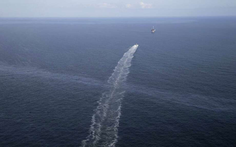 In this March 31, 2015 photo, the wake of a supply vessel heading towards a working platform crosses over an oil sheen drifting from the site of the former Taylor Energy oil rig in the Gulf of Mexico, off the coast of Louisiana.  (AP Photo/Gerald Herbert) Photo: Gerald Herbert, STF / AP