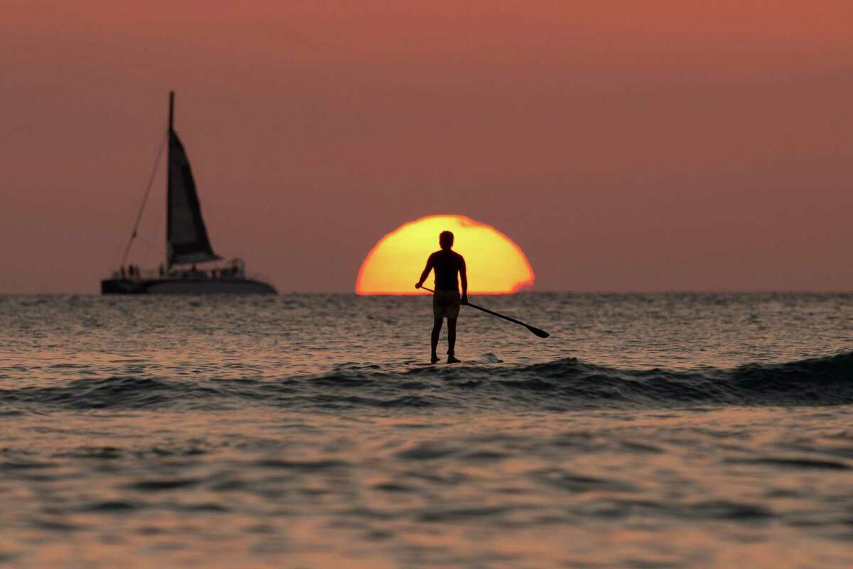 A paddle boarder looks our over the Pacific Ocean as the sun sets off of Waikiki Beach, in Honolulu, on New Years Eve, Tuesday, Dec. 31, 2013. (AP Photo/Carolyn Kaster)