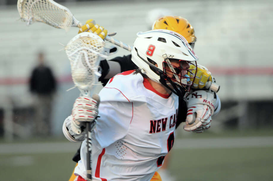 New Canaan's Owen Toland pushes past a Bruins defender as the Rams host the Brunswick Bruins in a boys lacrosse game in New Canaan, Conn., April 16, 2015. Photo: Keelin Daly / Stamford Advocate Freelance