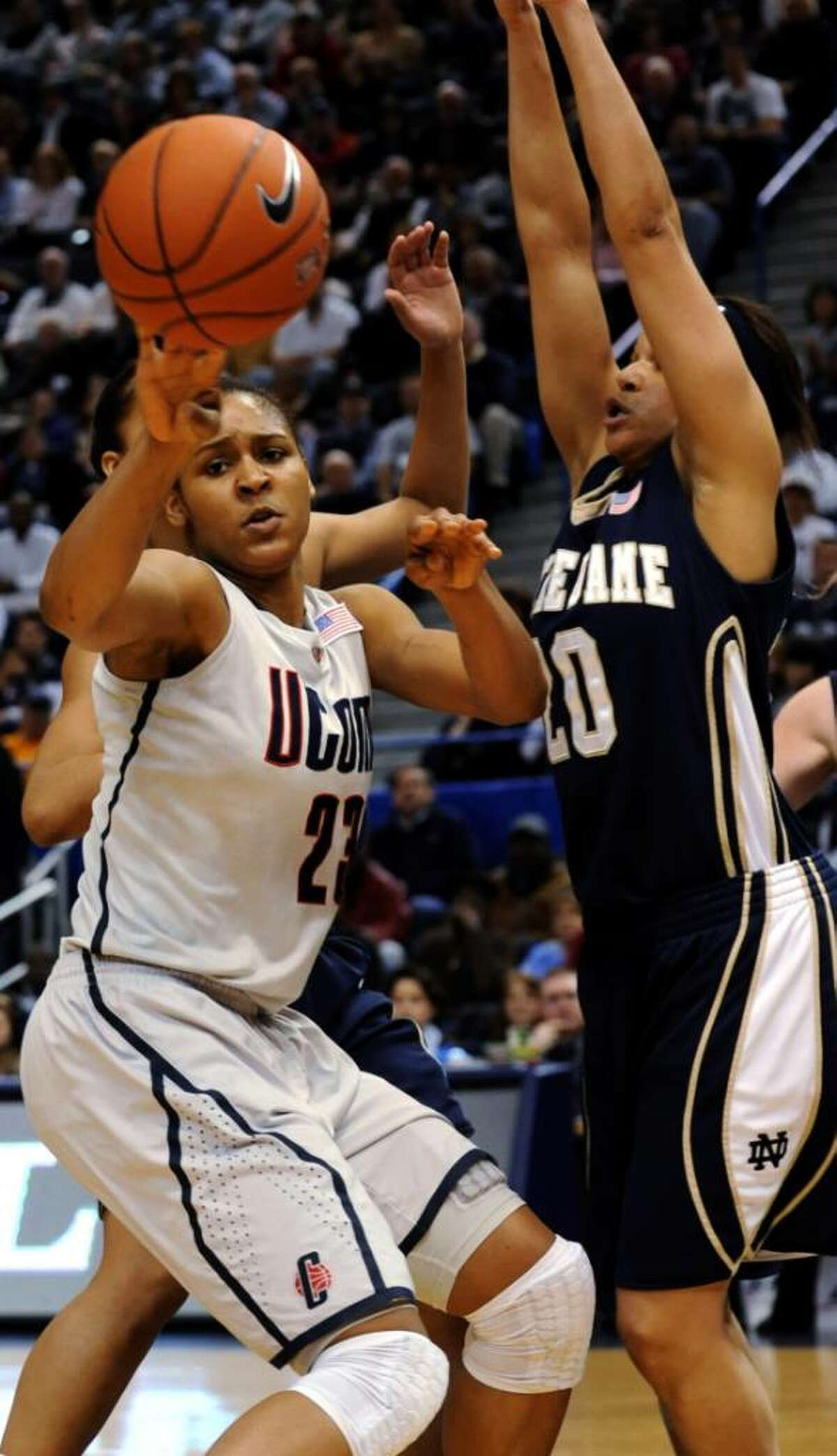 Connecticut's Maya More looks for a teammate to pass to as Notre Dame's Ashley Barlow defends during the first half of an NCAA college basketball game in the semifinals of the Big East tournament in Hartford, Conn., Monday, March 8, 2010. (AP Photo/Bob Child)