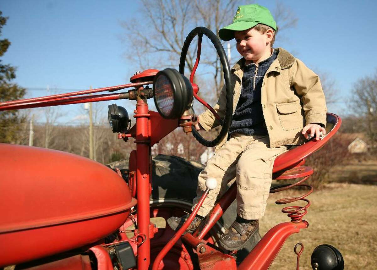 Sam Jones, seventh generation of Shelton's Jones farming family, has a seat atop a Farmall tractor at Bomba's Farm in Seymour, site of Governor M. Jodi Rell's visit on Monday, March 8, 2010.