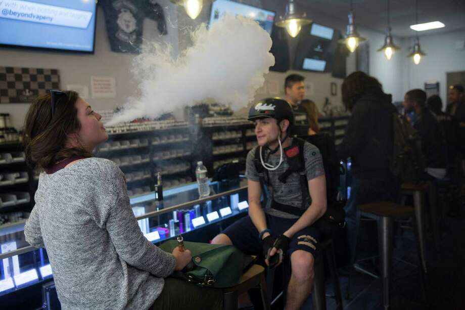 Customers smoke e-cigarettes at Beyond Vape, a store in New York, April 16, 2015. Some 13 percent of middle-and-high school students are using e-cigarettes, a sharp rise that led to an overall increase of teens using tobacco products, the first in years. (Michael Appleton/The New York Times) ORG XMIT: XNYT93 Photo: MICHAEL APPLETON / NYTNS