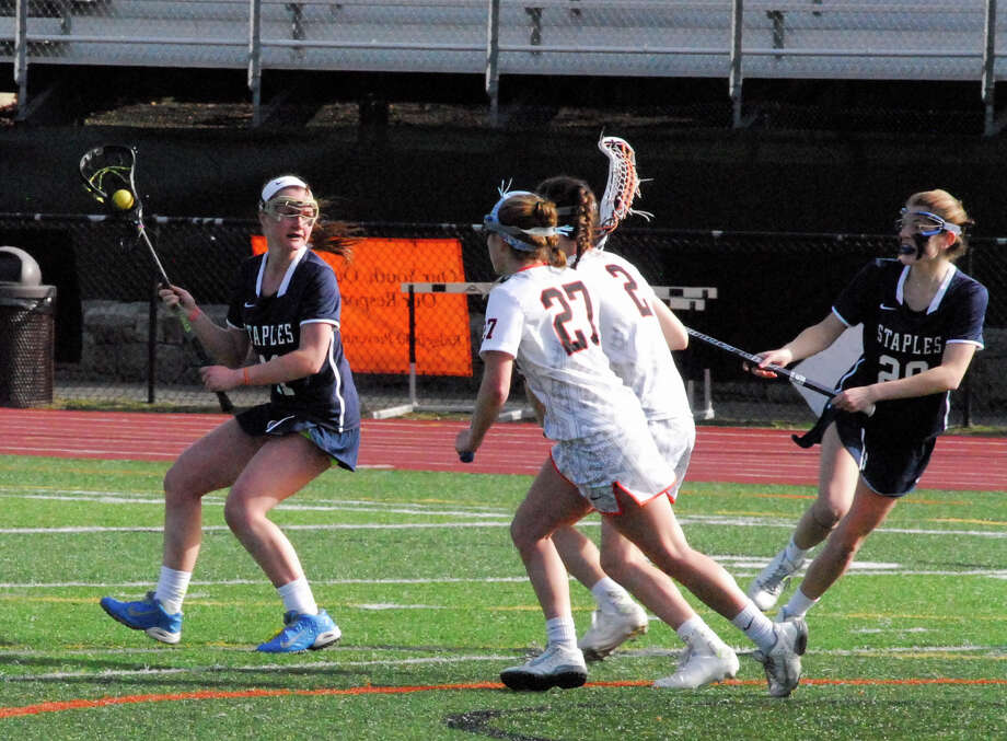 Staples sophomore Colleen Bannon, left, looks to make a play to teammate Nicki Najarian, right, while Ridgefield's Sarah Kaiser (27) and Kimmy Weinstock (2) look on during a game on Thursday. Ridgefield won 11-8. Photo: Ryan Lacey/Staff / Westport News Contributed
