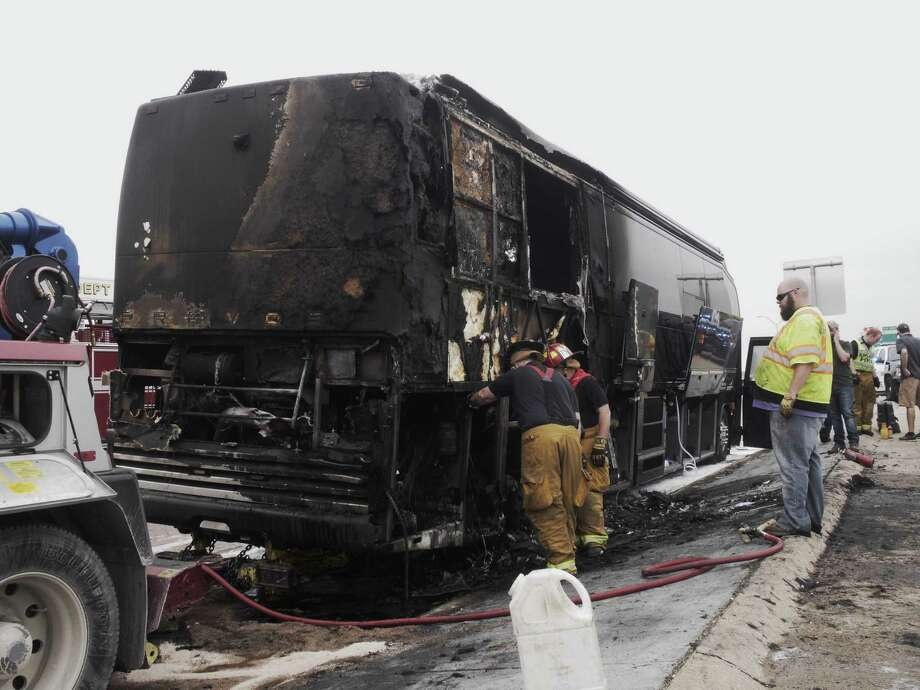 Garland firefighters extinguish a fire on a tour bus for superstar country group Lady Antebellum, Thursday, April 16, 2015 on eastbound I-30 in Garland, Texas. Singer Hillary Scott posted on the group's Facebook page that she, her husband, their tour manager and the driver were on the Dallas-bound bus when a tire caught fire.  Scott says everyone safely evacuated,  Garland police say the driver stopped the bus after the tire blew, and the vehicle caught fire on Interstate 30 just east of Dallas. Police confirm that nobody was injured. (Ron Baselice/The Dallas Morning News via AP) MANDATORY CREDIT; MAGS OUT; TV OUT; INTERNET USE BY AP MEMBERS ONLY; NO SALES ORG XMIT: TXDAM102 Photo: Ron Baselice / The Dallas Morning News
