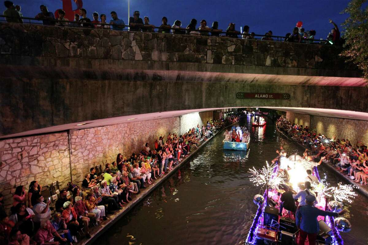 """Spectators watch the 2014 Texas Cavaliers River Parade """"River Wild"""" on April 21, 2014."""
