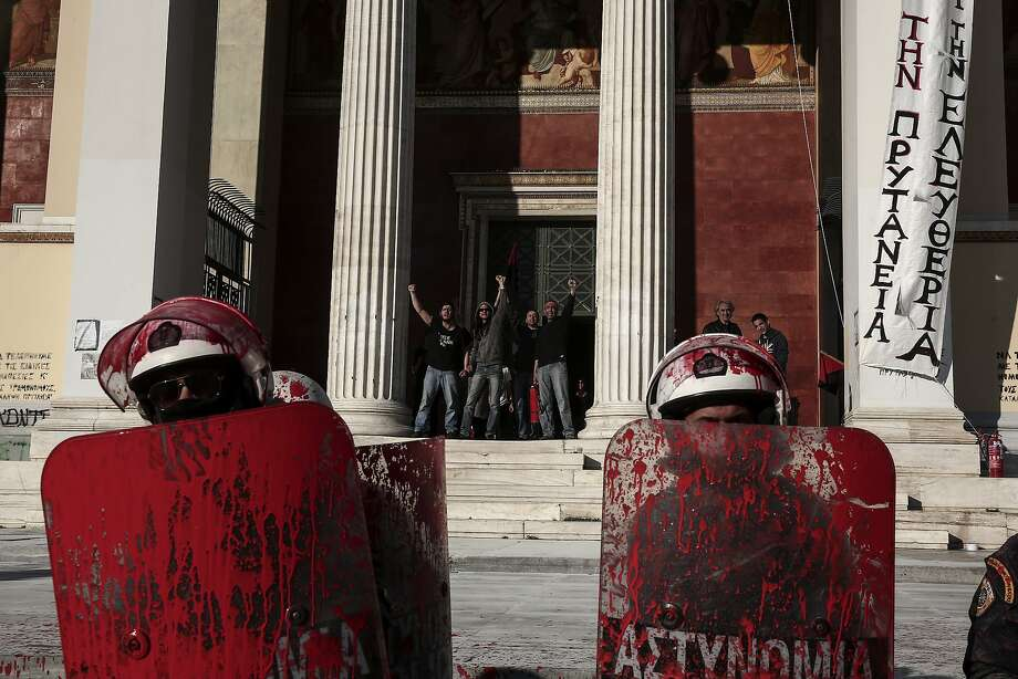 Protesters who have occupied the Athens University, shout from behind as police with their shields covered with red paint face-off against demonstrators during rally by their supporters, in Athens, Thursday, April 16, 2015. Leftist and anarchist groups seeking the abolition of new maximum security prisons, clashed in central Athens Thursday with riot police, who responded with tear gas and stun grenades. Photo: Yorgos Karahalis, Associated Press