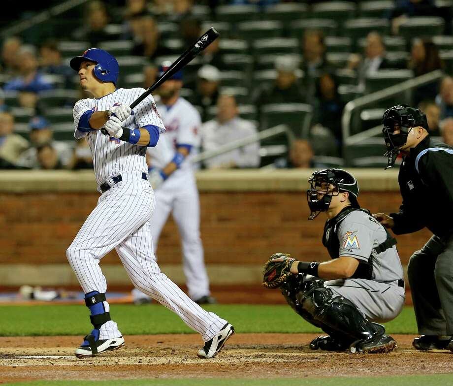 NEW YORK, NY - APRIL 16:  Wilmer Flores #4 of the New York Mets hits a three run homer in the fifth inning as Jacob Realmuto #20 of the Miami Marlins defends on April 16, 2015 at Citi Field in the Flushing neighborhood of the Queens borough of New York City.  (Photo by Elsa/Getty Images) ORG XMIT: 538577561 Photo: Elsa / 2015 Getty Images
