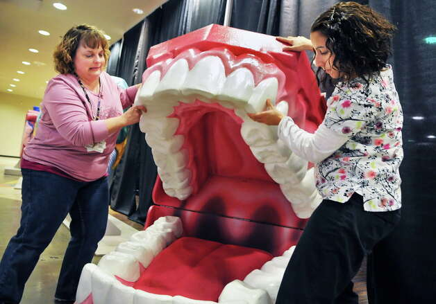 St. Peter's physical therapist Nancy Hellman, left, and speech pathologist Tiana Pendleton ready a set of giant teeth as part of the Journey Through the Body exhibit at Colonie Center in Colonie Thursday afternoon March 31, 2011. Opening Friday, the exhibit allows children to explore large-than-life-size models of the human body.   (John Carl D'Annibale / Times Union archive) Photo: John Carl D'Annibale / 00012591A