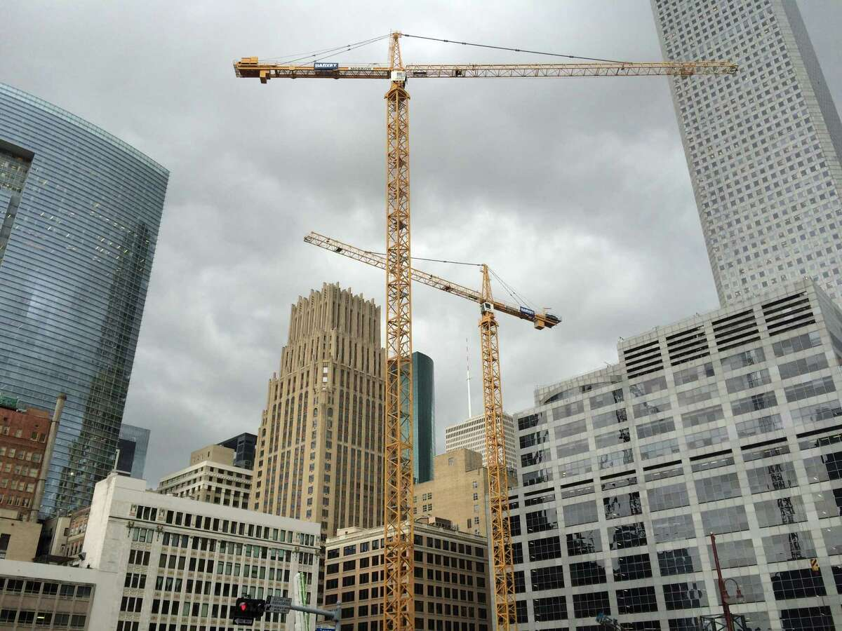 Cranes tower above a downtown skyscraper construction site. The location will house an office tower developed by Hines, which is also building a residential high-rise in nearby Market Square.