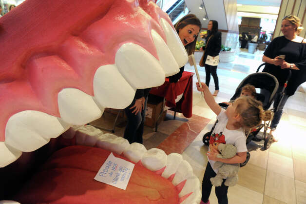 Four-year-old Gianna Dambrosio of Albany brushes a set of giant teeth as she is helped by dental hygienist  Elizabeth Wyman during Journey Through The Body coordinated by clinicians from St. Peter's Health Partners at the Colonie Center on Friday April 167 2015 in Colonie, N.Y. (Michael P. Farrell/Times Union) Photo: Michael P. Farrell / 00031458A