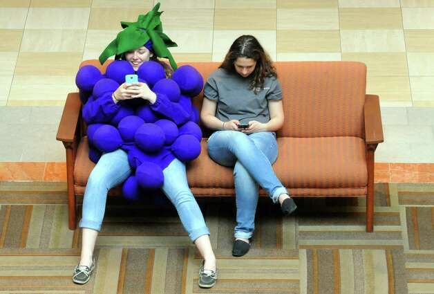 Sara Lausterbach, left, dressed as a bunch of grapes takes a break from her duties with friend Rory Byrnes during Journey Through The Body coordinated by clinicians from St. Peter's Health Partners at the Colonie Center on Friday April 167 2015 in Colonie, N.Y. (Michael P. Farrell/Times Union) Photo: Michael P. Farrell / 00031458A