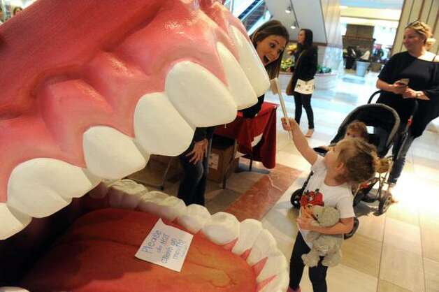 A child examines a massive set of teeth at Journey Through The Body which is coordinated by clinicians from St. Peter's Health Partners at Colonie Center. (Michael P. Farrell / Times Union)