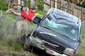 ADDS IDENTIFICATION OF DRIVER AND RESCUER- Jason Warnock, left, pulls Mathew Sitko, to safety from an SUV stopped by a chain link fence just short of a 30-foot vertical drop onto Bryden Canyon Road, Wednesday, April 15, 2015, in Lewiston, Idaho. The 23-year-old driver suffered minor injuries and was taken to a hospital, according to authorities. (Barry Kough/Lewiston Tribune via AP)