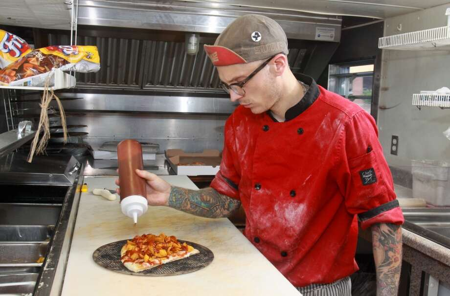 """Anthony Calleo topping a """"420 pizza"""" in his Pi Pizza Truck. He's moving his business out of the truck and into a restaurant by the end of the year. (Photo: Gary Fountain) Photo: Gary Fountain, For The Chronicle"""