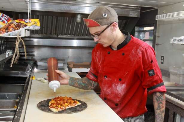 "Anthony Calleo topping a ""420 pizza"" in his Pi Pizza Truck. (Photo: Gary Fountain)"