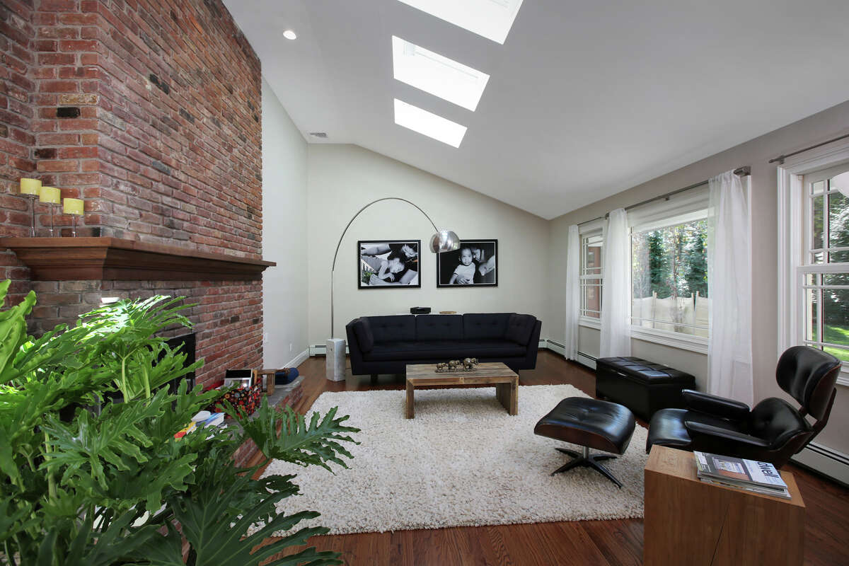 The living room features a floor-to-ceiling brick fireplace and skylights.