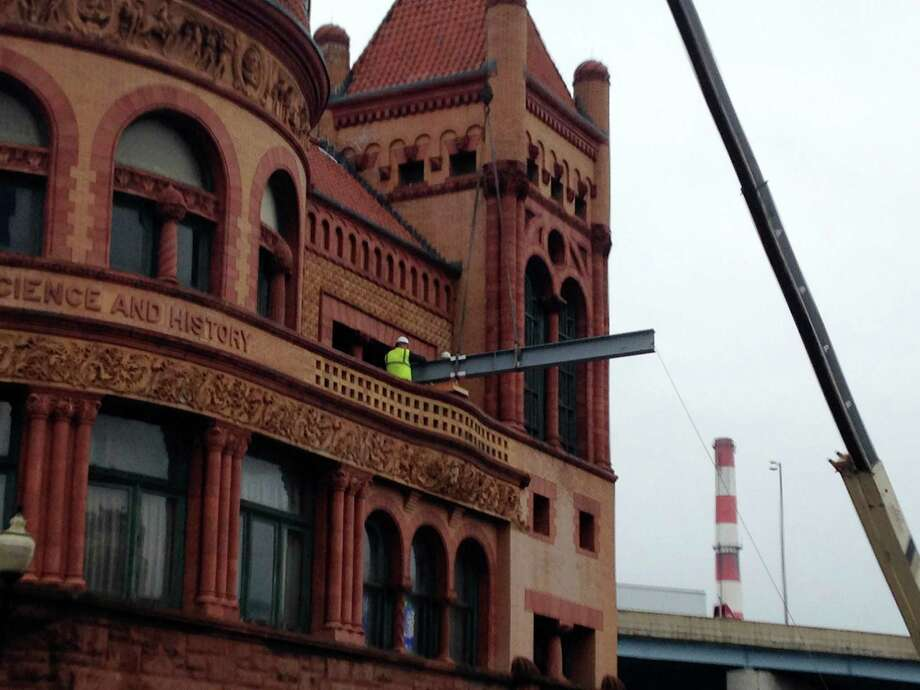 Three steel girders to support the roof of the historic Barnum Museum in Bridgeport, Conn. are hoisted through a third floor window, while traffic below on Main Street is diverted on Friday, April, 17, 2015. A June 2010 tornado caused structural damage to the 1892 building, and tropical storms Irene and Sandy added mud and water to the collection of artifacts. Photo: Frank Juliano / Connecticut Post
