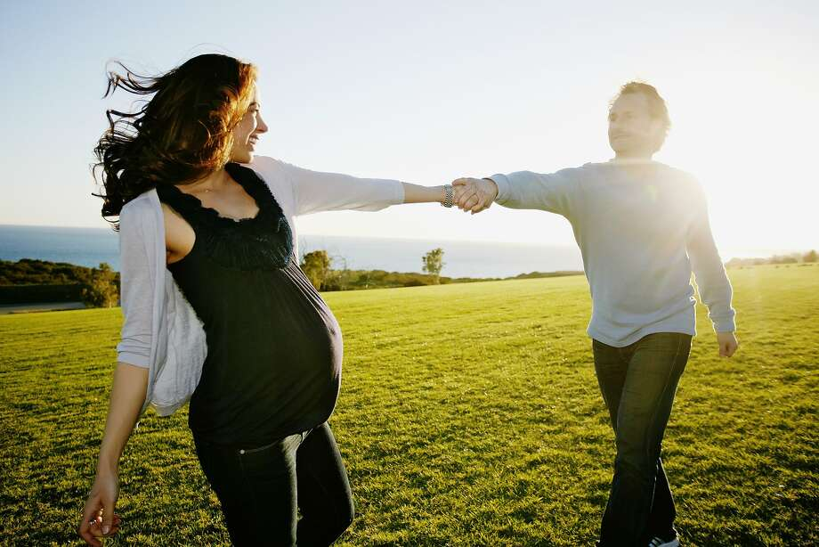 Pregnant couple playing in field Photo: Blend Images - Peathegee Inc