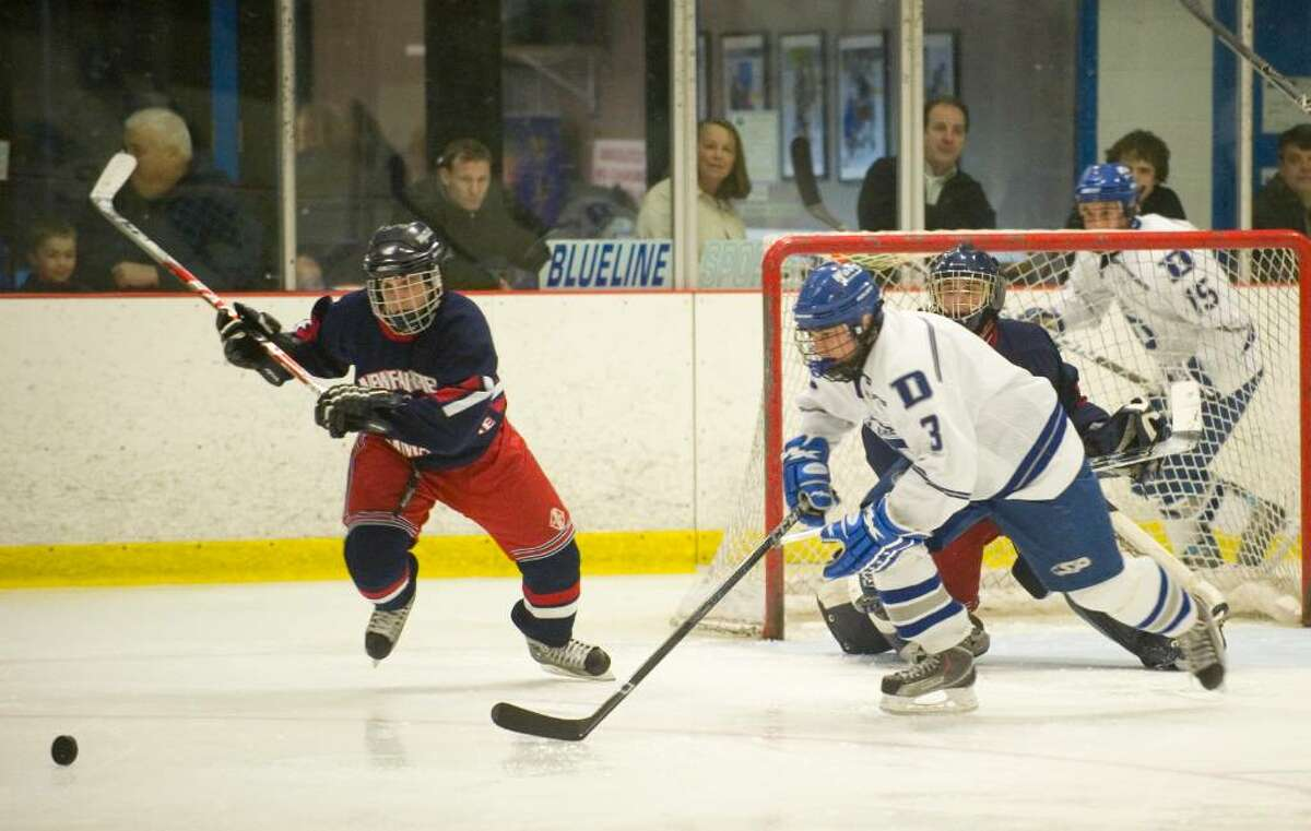 Immaculate's JJ DiTullio, left, and Darien's Domenick Luongo, right, go after the puck during the qaulifying round of the CIAC Division I boys ice hockey tournament in Darien, Conn. on Monday, March 9, 2010.