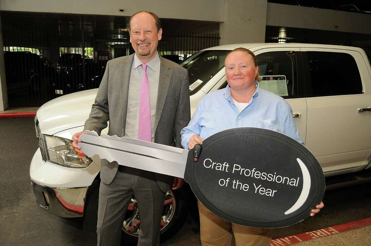 KBR CEO Stuart Bradie congratulates Holley Thomas after she won a Dodge Ram 1500 for being named Craft Professional of the Year at the KBR Building Thursday April 16, 2015.(Dave Rossman photo)