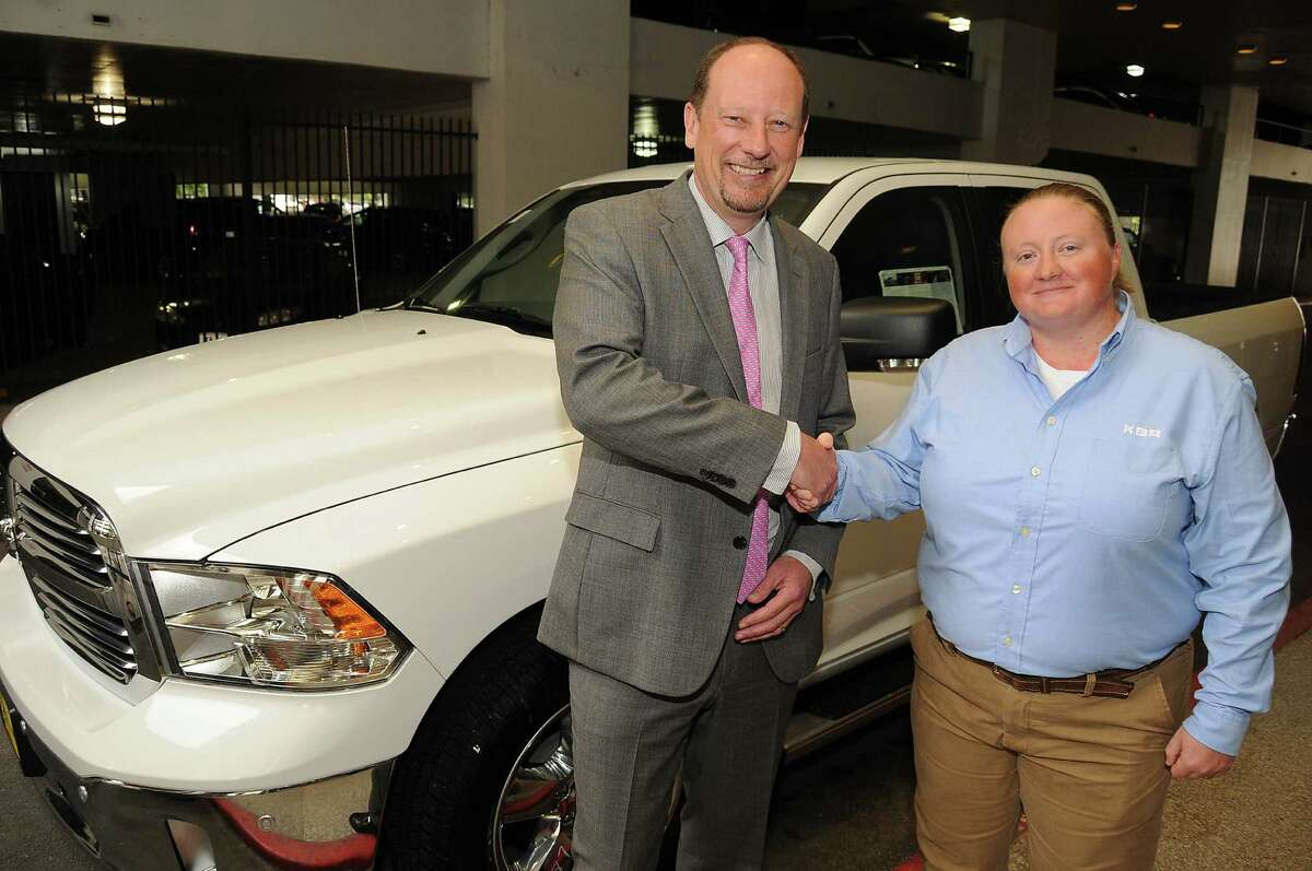 KBR CEO Stuart Bradie congratulates welder Holley Thomas after she won a Dodge Ram 1500 for being named Craft Person of the Year at the KBR Building Thursday April 16, 2015.(Dave Rossman photo)