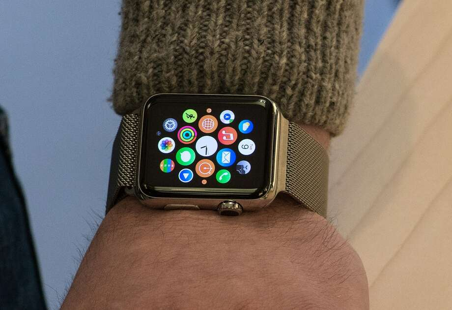"""(FILES) This April 10, 2015 file photo shows a customer as they try on an Apple watch in Washington, DC.  With the Apple Watch expected to sell in the millions, news organizations are refocusing their efforts to become part of that tiny screen. In the news business, this is now called """"glance journalism."""" The Apple Watch, expected to catapult to the leading item in wearable technology, opens up new possibilities to a news industry seeking to connect with audiences in the digital era. AFP PHOTO/NICHOLAS KAMMNICHOLAS KAMM/AFP/Getty Images Photo: NICHOLAS KAMM / AFP"""