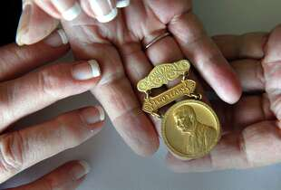 "Jill Carroll, returns a 100-year-old medal that she found 10 year's ago in a flea market suitcase to the Pam Stone the granddaughter of its rightful owner, as seen on Fri. April 17, 2015, in Sausalito, Calif. Stone and Carroll hold the medal which reads, ""For Two Years of Continvovs Service on the Panama Canal W.H. Stone"", the grandfather of Pam Stone."