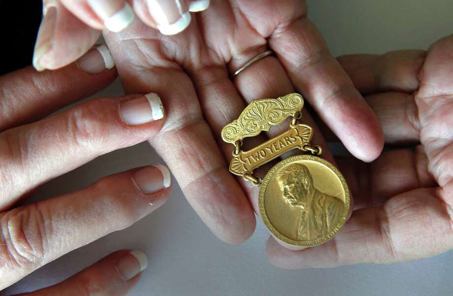"Jill Carroll, returns a 100-year-old medal that she found 10 year's ago in a flea market suitcase to the Pam Stone the granddaughter of its rightful owner, as seen on Fri. April 17, 2015, in Sausalito, Calif. Stone and Carroll hold the medal which reads, ""For Two Years of Continvovs Service on the Panama Canal W.H. Stone"", the grandfather of Pam Stone. Photo: Michael Macor / The Chronicle / ONLINE_YES"