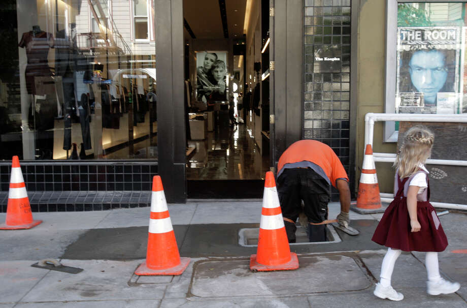 Isaiah Sinapopo, a contractor for Comcast, installs underground fiber-optic cables him in the Pacific Heights area on Fillmore Street in S.F. last year. Photo: Daniel E. Porter / The Chronicle / ONLINE_YES