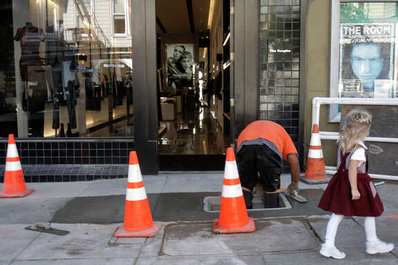 Isaiah Sinapopo, a contractor for Comcast, installs underground fiber-optic cables him in the Pacific Heights area on Fillmore Street in S.F. last year.