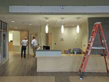 Dave Perrone, of ASI Signage,  left, and Charles Geyer, Facilities Director of New Milford Hospital, go over sign placement in the new Arnhold Emergency Department of New Milford Hospital, on Friday, April 17, 2015, in New Milford, Conn. .