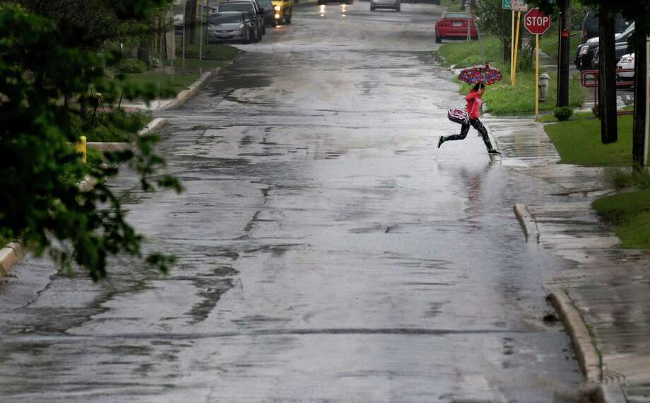 An umbrella-clad individual makes a leap over a puddle of water on Howard Street as thunder storms loomed over the city on Friday, Apr. 17, 2015. Photo: Kin Man Hui, San Antonio Express-News / ©2015 San Antonio Express-News